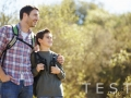 Father And Son Hiking In Countryside Wearing Backpacks